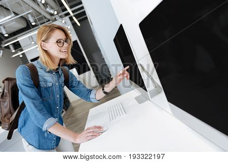 Radiant female shopper smiling and working with a mockup computer while shopping at an electronics section of a department store.
