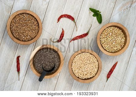 Wheat Berries Buckwheat Groats Pearl Barley Chia Seeds in Bowls with Red Peppers on the side