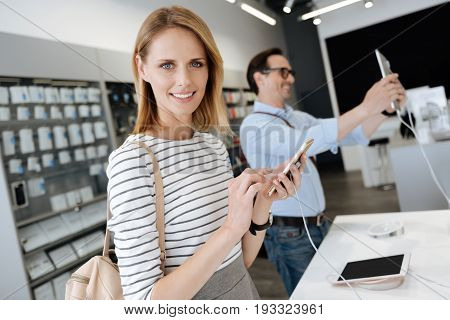 Cheerful grey eyed woman holding a mockup smartphone and looking into the camera while a male shopper wearing glasses taking selfies with a template tablet computer in the background.