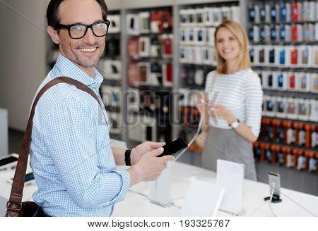 Radiant man wearing glasses beaming while posing for camera with a mockup smartphone in hands during a shopping outing.