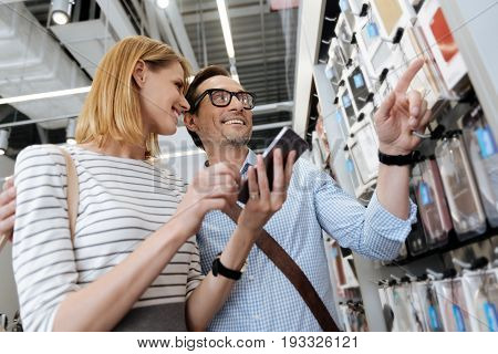 Low angle shot of an adorable couple embracing and beaming while shopping for a new smartphone cases at an electronics section of a department store.