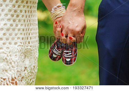 Future parents holding hands and a pair of little shoes overnature green background. Concept of Parents-To-Be.
