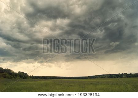 Storm Cloud Over Yellow Green Fields Forests And Hills