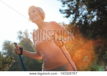 In the park. Joyful positive happy woman smiling and holding Nordic walking poles while enjoying being outdoors