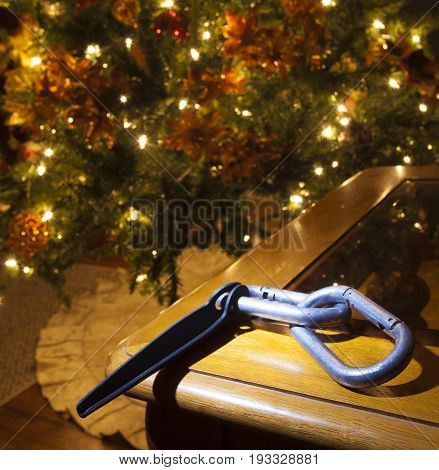 Carabiners and piton on table with a Christmas tree behind