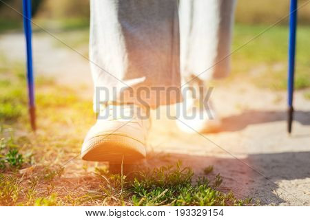 Only forward. Close up of a persons feet making a step while doing Nordic walking in the park