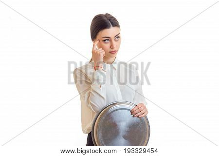 a young thoughtful waitress looks away and keeps the tray is isolated on a white background