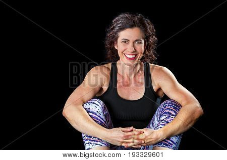 A happy muscular woman sits with her arms resting on her knees and hands clasped. She is on a black background and is back lit. There is a path around her.