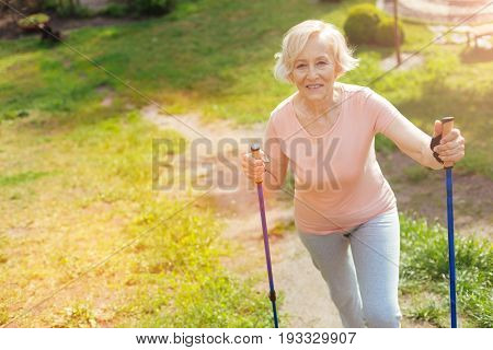 Positive mood. Delighted positive elderly woman smiling eng enjoying her walk while being in the forest