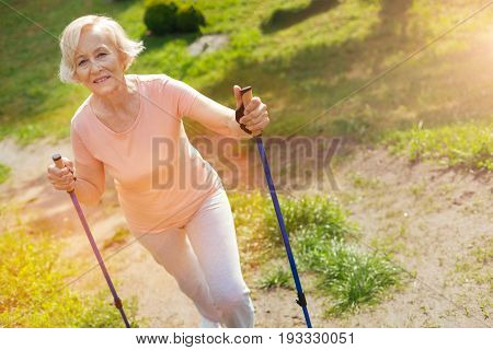 Nordic walking equipment. Happy delighted positive woman using walking poles and smiling while practicing outdoor activities