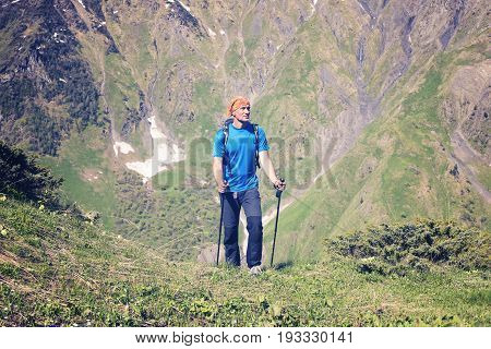 Satisfied Traveler Climbs The Green Slope, In A Mountain Gorge