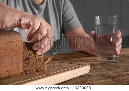Elderly woman pinching off a piece of bread at table. Poverty concept