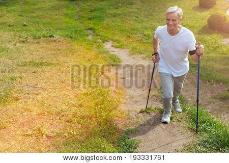 Active lifestyle. Positive joyful aged man holding walking poles and hiking while leading an active lifestyle