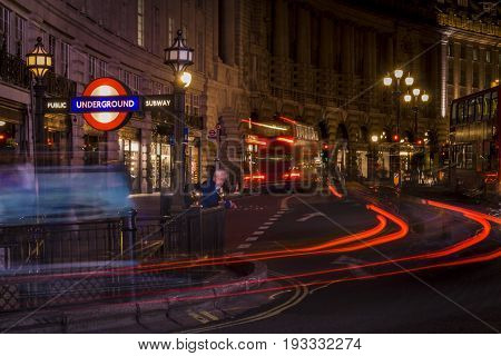 London, UK, March 11 2009: Quiet scene of Subway station in Regent street at night with cars and buses lighttrails