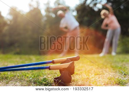 Nordic walking equipment. Nordic walking poles lying on the ground with active sporty senior couple exercising in the background