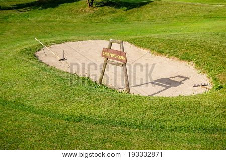 Chipping green sign in front of bunker on golf course, detail of golf ground
