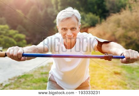 Useful sports equipment. Cheerful active aged man leaning forwards and smiling while exercising with a walking pole