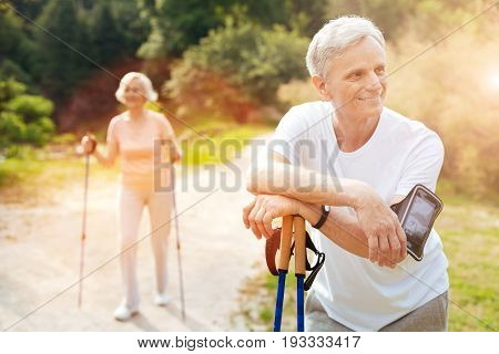 Time to rest. Happy delighted cheerful man leaning on the walking poles and smiling while resting after the workout