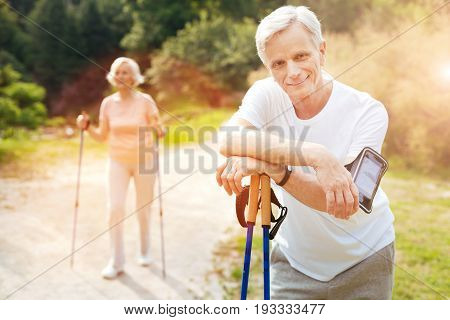 During the workout. Handsome delighted elderly man leaning in the walking poles and looking at you while having a break from the workout