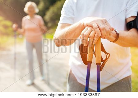 Ready to train. Close up of male hands being put on the walking poles while having an outdoor workout