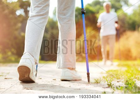 Professional training. Close up of a Nordic walking pole being in use by an active sporty person while doing sports exercises