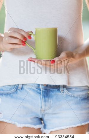 Girl holding a cup od tea / coffee outdoors. Shallow depth of field on the hand.