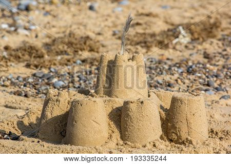 Vacation memory Abandoned sand castle on seaside resort beach. Holiday memories represented by a sandcastle.