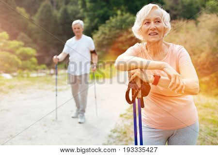 After a workout. Cheerful pleasant senior woman leaning on her walking poles and smiling while standing in front of her husband