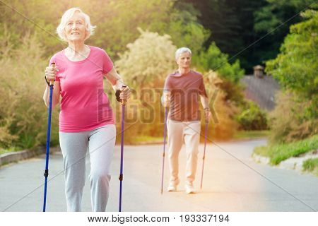 Outdoor training. Positive active nice couple holding walking poles and practicing sports activities while having an outdoor training
