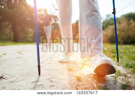 Movement is life. Nice active aged man holding walking poles and making a step forward while practicing sport activities