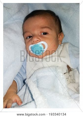 two months old baby boy in puschair facial expresion confused, happy,