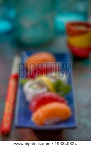 Blurry background image. Sushi nigiri and California Roll on a blue plate