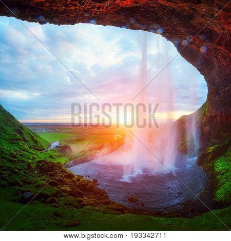 Sunrise on Seljalandfoss waterfall on Seljalandsa river, Iceland, Europe. Amazing view from inside