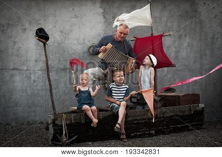 Three cute dude with their daddy playing pirates on a wooden boat on a summer evening