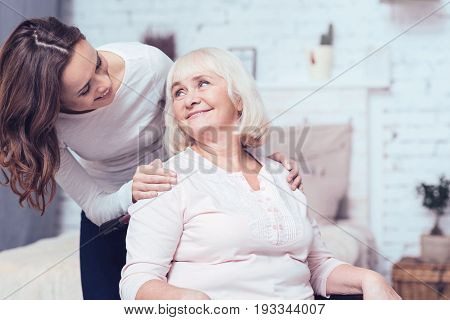Full of positive feelings. Appreciative positive young woman standing in the bedroom and taking care of aged disabled grandmother while hugging