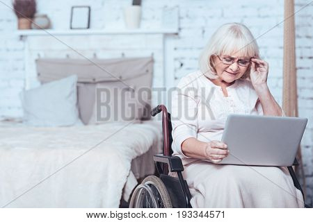 Testing modern technologies. Concentrated aged enable woman sitting in the wheelchair at home while expressing interest and using laptop