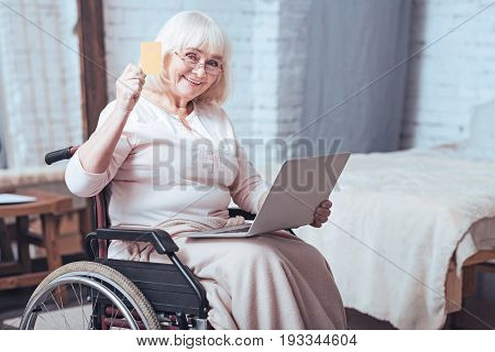 Full of happiness . Smiling aging enable woman sitting in the wheelchair at home while expressing interest and using laptop