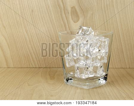 Glass of ice with a wooden background