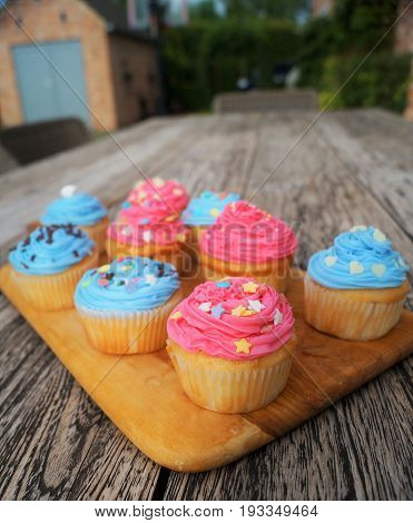 Pink and Blue Cupcakes. Homemade colorfully decorated pink and blue cupcakes on a rustic outdoor wood picnic table