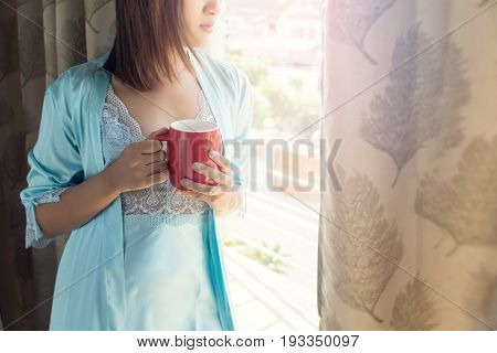 Woman sitting at opened window drinking coffee and looking outside enjoys of rest
