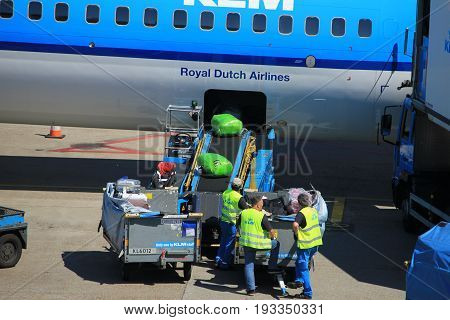 Amsterdam The Netherlands - May 26th 2017: KLM Boeing 737 parked at gate at Schiphol International Airport luggage handling