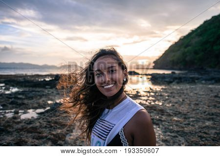 EL NIDO, PALAWAN, PHILIPPINES - MARCH 29, 2017: The amazing colorful sunset of Las Cabanas Beach with a mixed race girl.