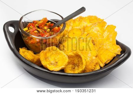 Plantain cups and patacones with hogao on white background