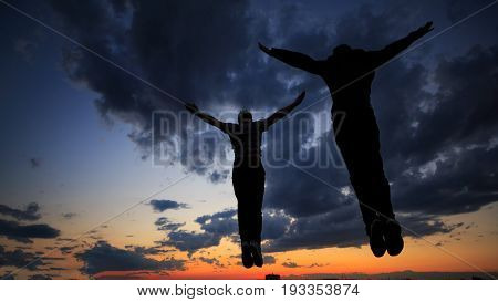 Silhouettes of mens against the background of clouds and golden sunset. They jump on the roof. Parkour in the evening.