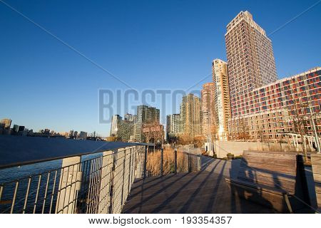 Walkway and fence's shadow at Gantry Plaza State Park and buildings