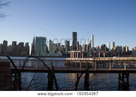 Cityscape of Manhattan and pier at Gantry Plaza State Park over East river with blue sky
