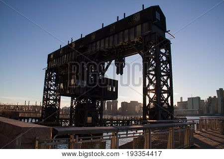 Silhouette of iconic gantries of Gantry State Park and Manhattan under sunset sky