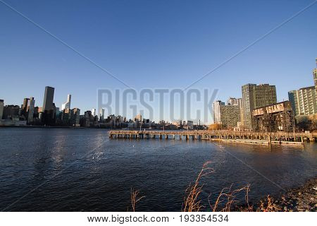 Pier on East river at Gantry Plaza State Park and buildings of Manhattan over East river