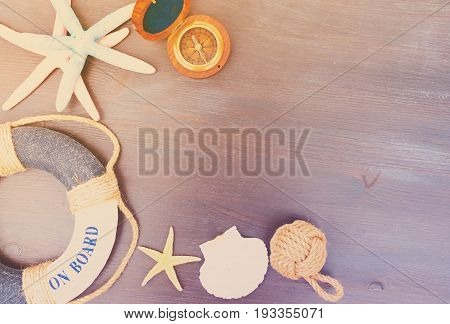 Old vintage compass with marine knot, life-ring and seastars with copy space on wooden table, retro toned
