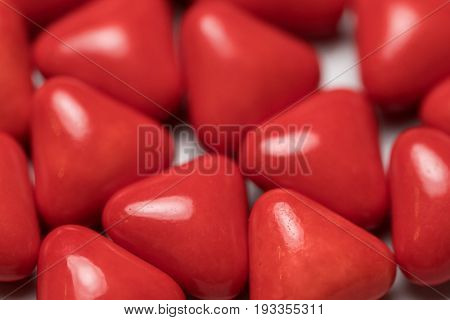 Closeup of red triangle pills looking like heart shaped candy isolated over white background
